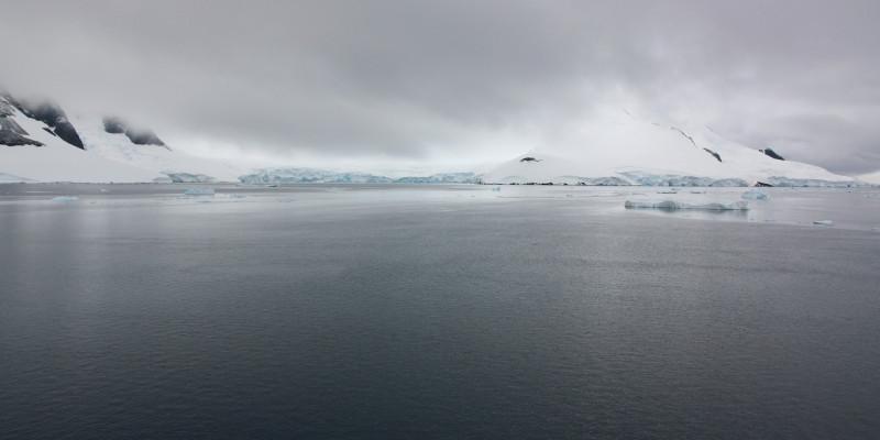 Über dem Wasser bilden sich Unwetterwolken. Das Wasser ist schon fast schwarz. Im Hintergrund sieht man einen Berg, von Schnee bedeckt.
