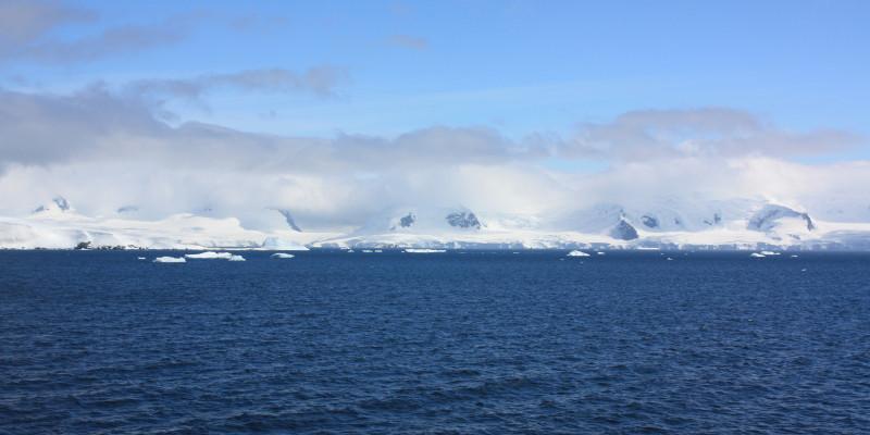 Eine weiße Wolkenschicht umgibt antarktische Berge an der Küste. Darüber sieht man eine zweite dunkler und dünnere Wolkenschicht.
