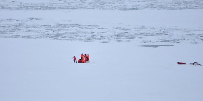 Eine Gruppe von Forschern in orangenen Kälteschutzanzügen steht auf einer großen Eisfläche. Rechts von ihnen, am Bildrand steht ihre Ausrüstung.