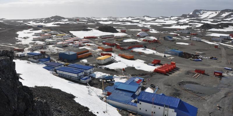 Von einer Erhöhung sind Forschungsstationen auf der Fildes-Halbinsel aufgenommen. Der Boden ist größtenteils schneefrei. Die Stationen haben verschiedene Farben: rot, blau und weiß.