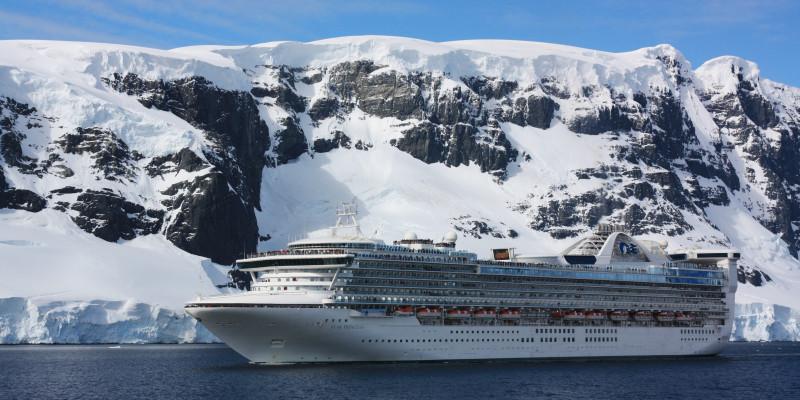 Vor einer schnee- und eisbedeckten Felsenwand fährt ein Kreuzfahrtschiff. Das Wasser ist ruhig, der Himmel ist klar.