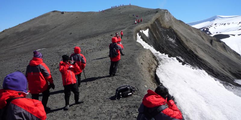 Touristen in roten Funktionsjacken erklimmen einen Hügelgrat. Der Hügel ist nur zur Hälfte schneebedeckt. Einige Leute machen Photos.