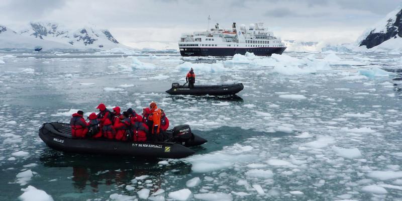 Das antarktische Meer ist mit vielen kleinen Eisschollen und Eisstücke bedeckt. Im Wasser fahren zwei Zodiacs. Im Hintergrund wartet das Kreuzfahrtschiff.