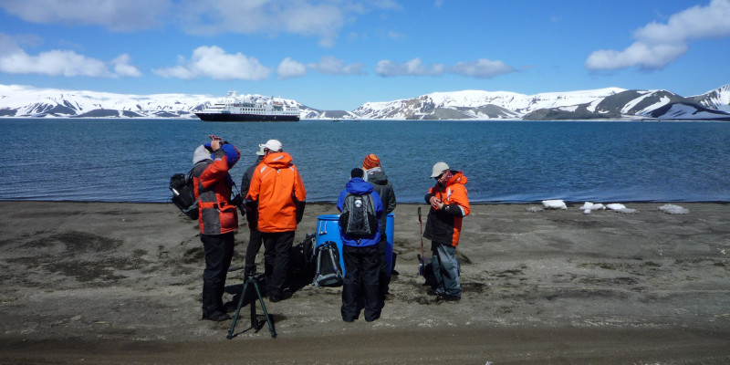 Reisende stehen im Vordergrund auf Land. Im Hintergrund sieht man antarktisches Meer und ein großes Schiff vor beschneiten Hügeln.
