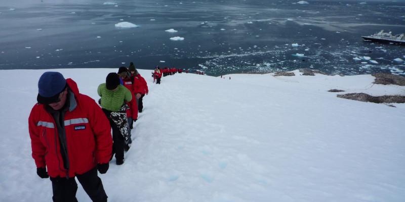 Auf der linken Seite des Bildes kommen Menschen eine schneebedeckte Höhe hochgelaufen. Sie laufen in einer Reihe hintereinander.  Auf dem Meer sieht man das Schiff von dem aus sie gestartet sind.
