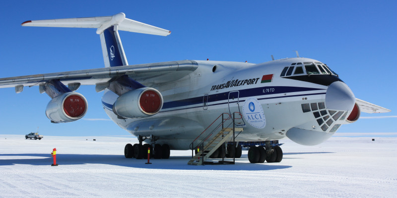 Ein weißes Transportflugzeug mit blauen Streifen an der Seite steht auf der Start- und Landebahn in der Antarktis. Eine Treppe steht vor der Tür. Im Hintergrund fährt ein Pick-up.
