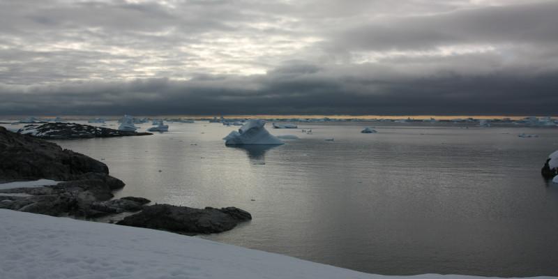 Über im Wasser schwimmenden Eisschollen zieht ein Gewitter ab.