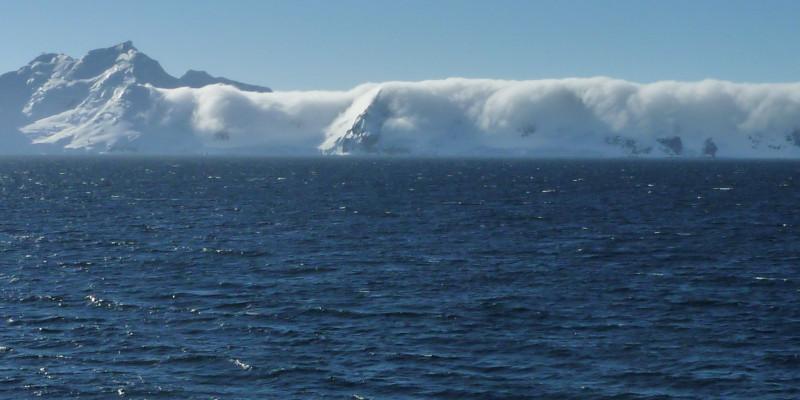 im Vordergrund des Bildes sieht man ruhiges antarktisches Meer. Im Hintergrund des Bildes schließen Berge an, die fast vollständig von Wolken eingehüllt sind.