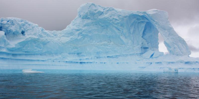Im fast schwarzen Wasser schwimmt ein hellblau anmutender Eisberg. Der Himmel wirkt grau und trist.