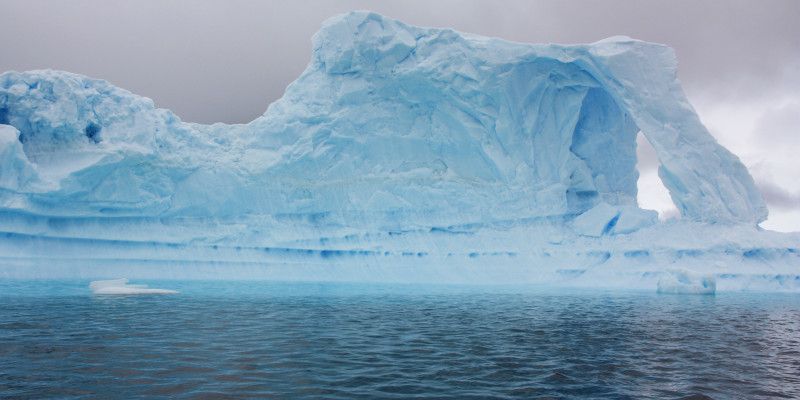 An appealing light blue iceberg floats in the nearly black water. The sky is gray and drab.