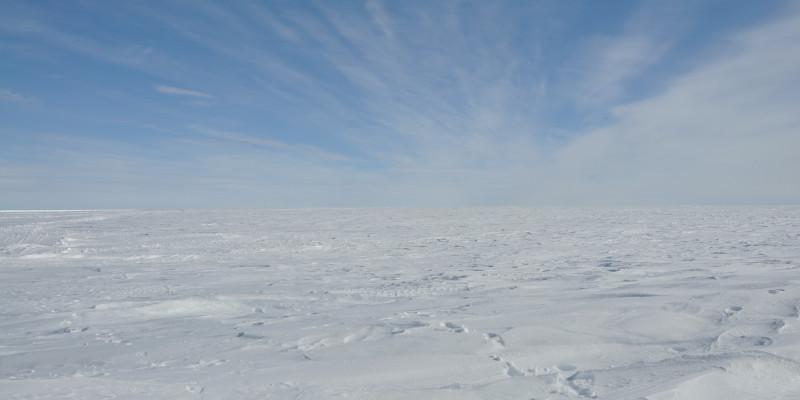 Eine Eisschicht so weit das Auge reicht. Der Himmel ist bilderbuchblau und nur eine dünne Wolkenschicht ist am Horizont zu sehen.