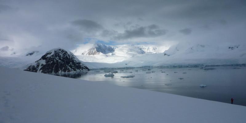 Im Vordergrund Schnee und Eis. Über dem Meer eine fast geschlossene Wolkendecke. Durch die Öffnung ist blauer Himmel zu sehen.