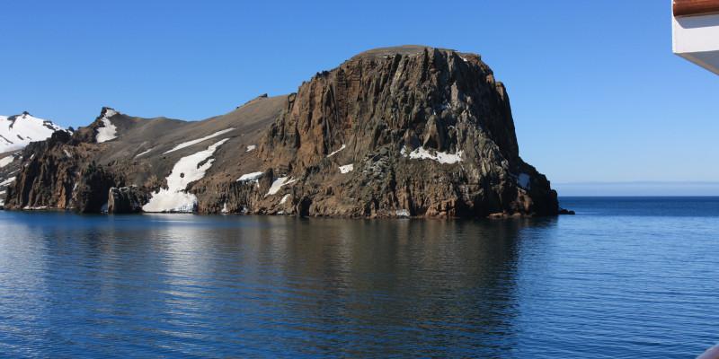 Blick von einem Schiff auf einen schroffen Berg, der aus der arktischen See ragt.