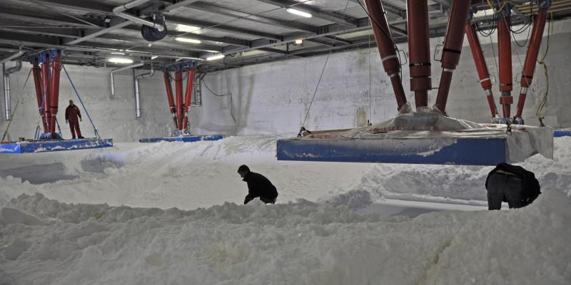 Drei Menschen arbeiten unter der Station Neumayer-III, um die Hydraulikstützen mit Schnee zu unterfüttern. Zwei Stelzen sind angehoben.