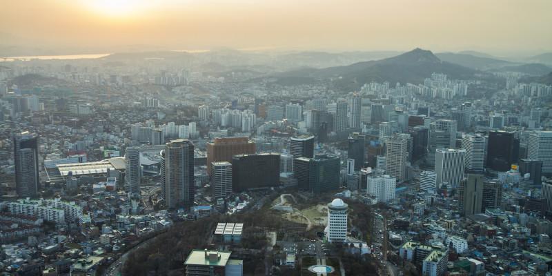 Blick über eine Großstadt, über der eine Smog-Wolke hängt; die Wolke verdecken fast die Sonne