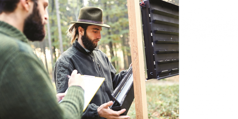 Das Bild zeigt zwei junge Förster, die eine Borkenkäferfalle kontrollieren. Einer hält eine Sammeleinrichtung, einer macht Aufzeichnungen in einem Notizblock.