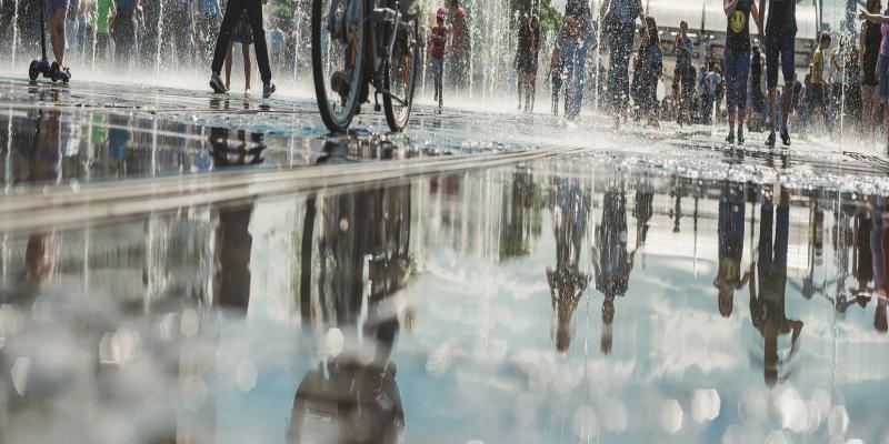 Das Bild zeigt eine Wasserfläche in eine Stadt, offensichtlich ein Brunnen. Es laufen mehrere Menschen über die Wasserfläche und spiegeln sich darin.