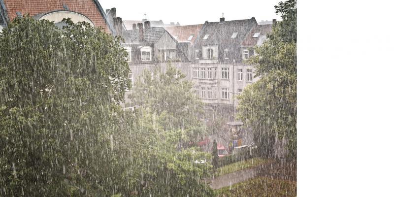 Das Bild zeigt den Blick auf eine Gruppe älterer mehrgeschossiger Gebäude und einige Bäume, die man durch einen gerade herabgehenden Starkregen kaum mehr erkennen kann.