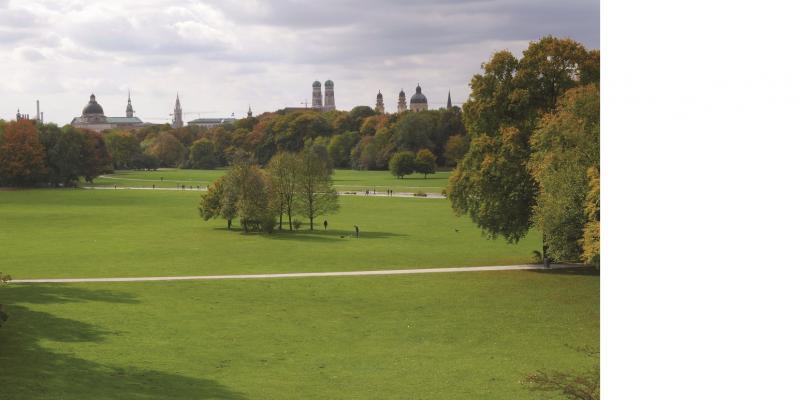 Das Bild zeigt den Blick in den Englischen Garten in München. Man sieht große Wiesenflächen, die von Wegen durchzogen sind und auf denen einzelne Baumgruppen stehen. Im Hintergrund sieht man die Stadtsilhouette von München.