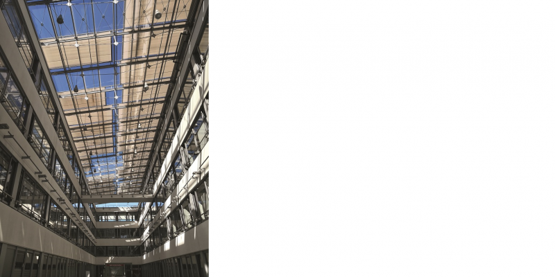 The picture shows the view to the glass roof of an inner courtyard of a modern building, which is partially shaded by textile panels.