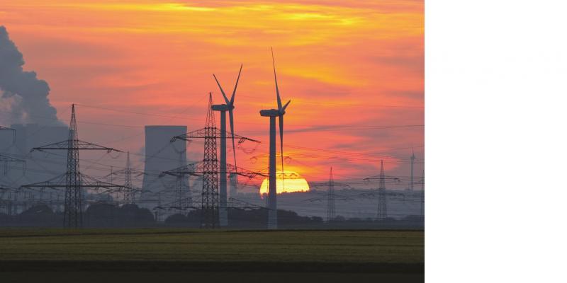 Das Bild zeigt gegen die untergehende Sonne zwei Windkraftanlagen, einen Kühlturm und mehrere Strommasten.