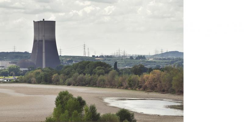 Das Bild zeigt ein nahezu trockengefallenes Flussbett, das von Baumreihen gesäumt ist. Im nahen Hintergrund erhebt sich ein Kühlturm.