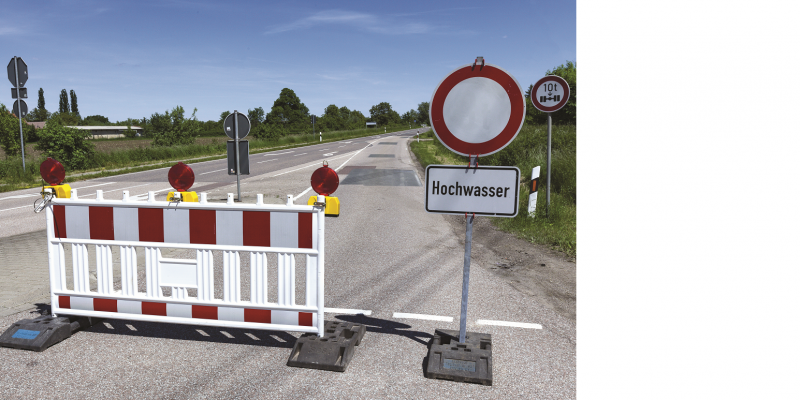 The picture shows an empty road. In the foreground it is closed off with a roadblock and a barrier sign with the inscription flood.