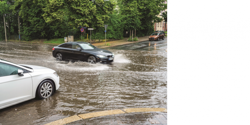 The picture shows a completely flooded street crossing in a city, into which two cars are just driving.