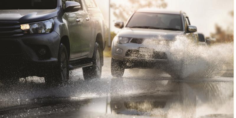 Das Bild zeigt in Großaufnahme eine mit Wasser bedeckte Fahrbahn. Ein Auto fährt gerade beinahe auf ein anderes auf.