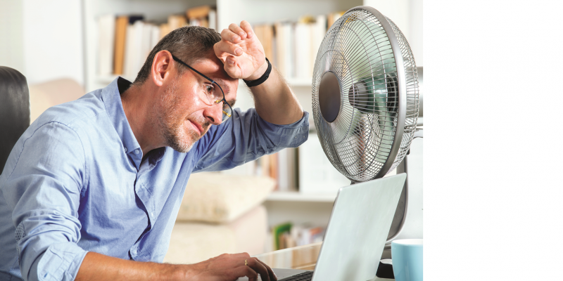 The picture shows a man sitting in front of a fan in an office, holding the back of his hand to his forehead.