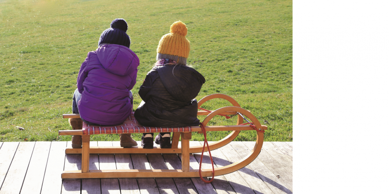 The picture shows two children from behind, wearing bobble hats and winter jackets, sitting next to each other on a sledge that is standing on a wooden terrace in front of a green meadow.