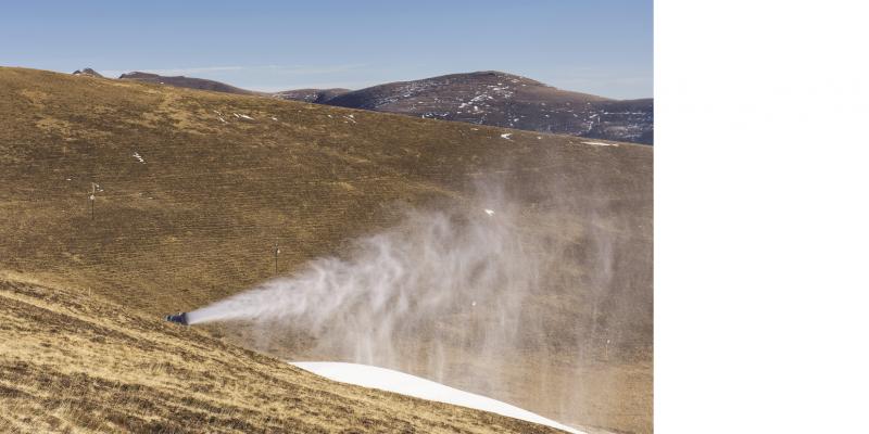 Das Bild zeigt eine in Betrieb befindliche Schneekanone in einem bergigen Pistengelände, auf dem kein Schnee liegt.