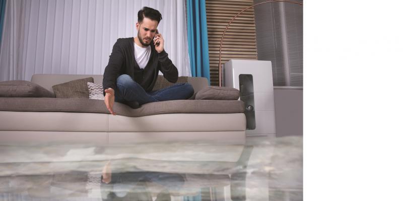 Das Bild zeigt einen auf einem Sofa im Schneidersitz sitzenden und telefonierenden Mann. Auf dem Boden des Raumes steht Wasser. Der Mann zeigt vorwurfsvoll auf die Wasserfläche.