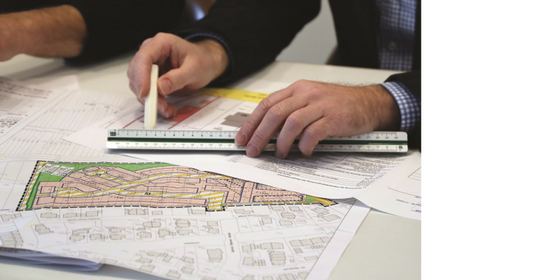 The picture shows two hands with a ruler and a pencil on a development plan spread out on the table.