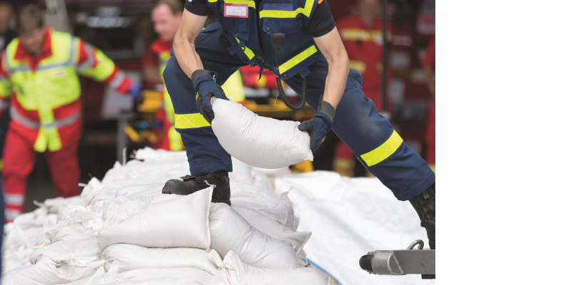 The picture shows emergency workers stacking sandbags.