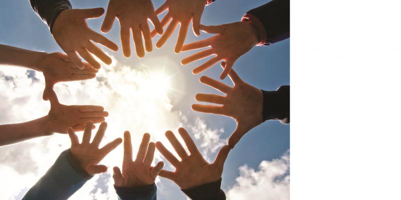 Das Bild ist in den Himmel gegen die Sonne gerichtet und zeigt einen Kreis von zehn aufgespannten Händen in einem Kreis.