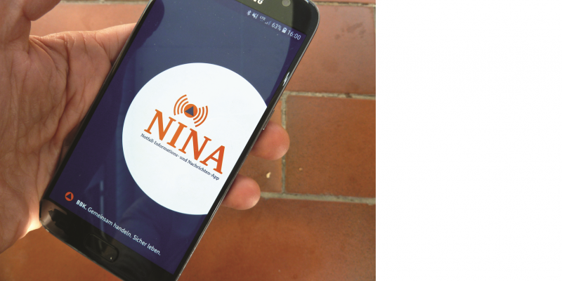 The picture shows a hand holding a smartphone. The NINA app is called up in it.