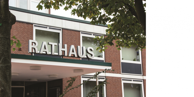 The picture shows a building clad in clinker bricks with the inscription Rathaus.