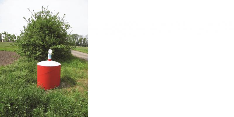 Das Bild zeigt eine Grundwassermessstelle in der Landschaft. Aus einem runden roten Sockel ragt ein Stutzen.
