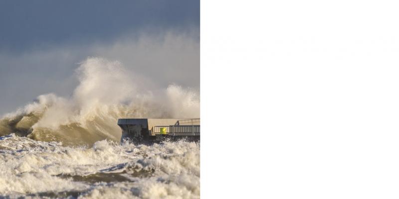 Das Bild zeigt eine Sturmflutwelle, die auf ein Küstenbauwerk aufschlägt. Das Meer ist insgesamt stark aufgewühlt.
