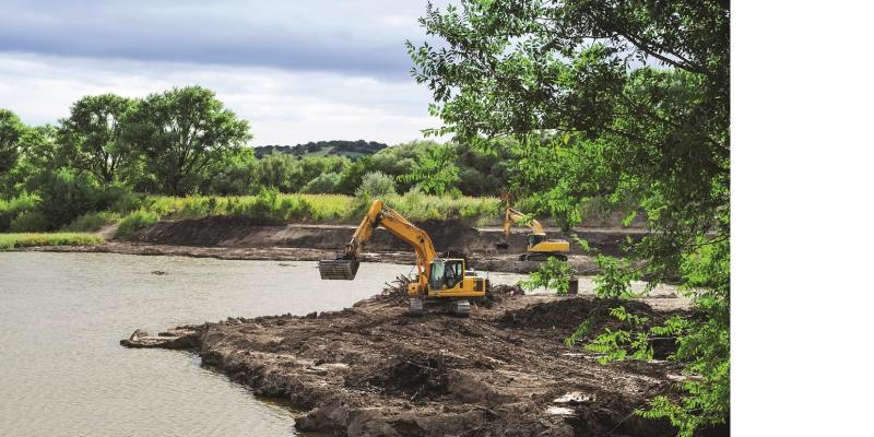 Das Bild zeigt ein Gewässer, an dessen Rand eine Baumaßnahme durchgeführt wird. Der Uferrand ist offener Boden, auf dem zwei Bagger aktiv sind.