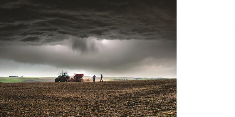 Das Bild zeigt im Vordergrund einen Acker. Ein Traktor sät gerade und zwei Männer kontrollieren die Einsaat. Im Hintergrund ist eine weiter landwirtschaftlich genutzte Landschaft zu sehen. Der Himmel ist sehr dunkel, es naht ein Gewitter.