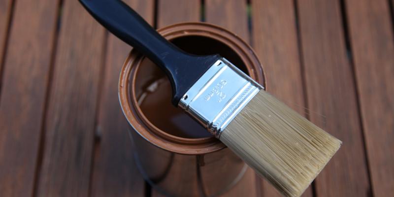 Ein Eimer mit Holzlasur, auf ihm liegt ein Pinsel, im Hintergrund Holzpaneelen.
