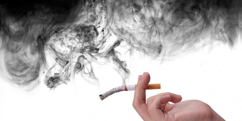 Hand mit Zigarette und Rauchschwaden