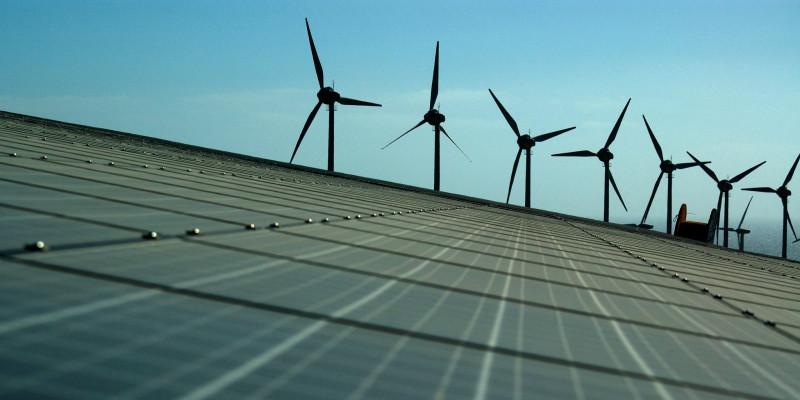Eine Solaranlage auf freien Feld, im Hintergrund drehen sich Windkrafträder