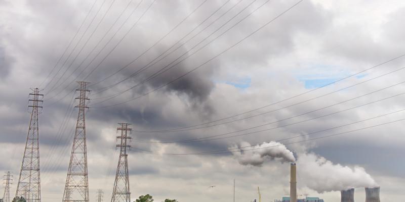 Wolkige Landschaft mit Stromnetzen und Kraftwerk