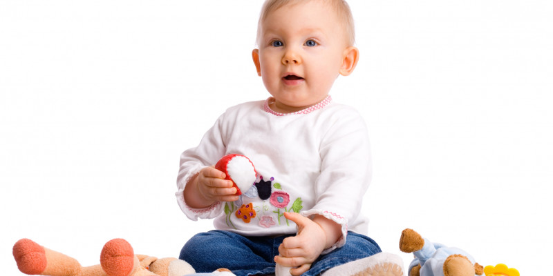 A baby sits among cuddly toys with a ball in its hand.