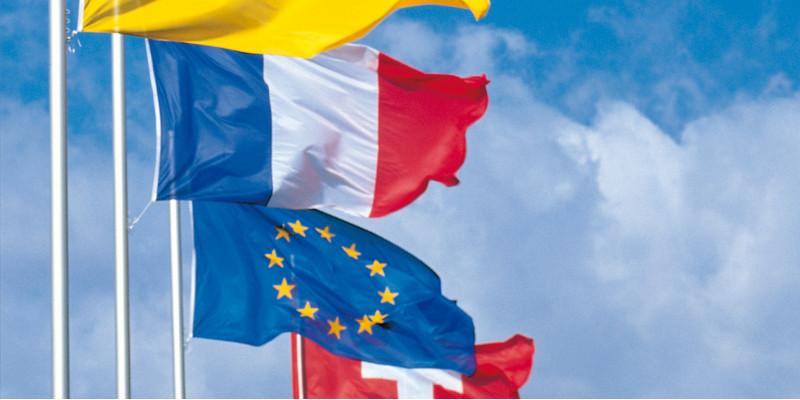 Wehende Flaggen in einer Reihe von vorn nach hinten: Badische Flagge, Frankreich, Europa und Schweiz vor einem blauen Himmel