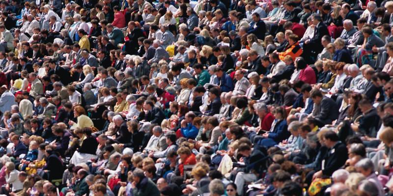 Viele Menschen sitzen nebeneinander und schauen in die selbe Richtung