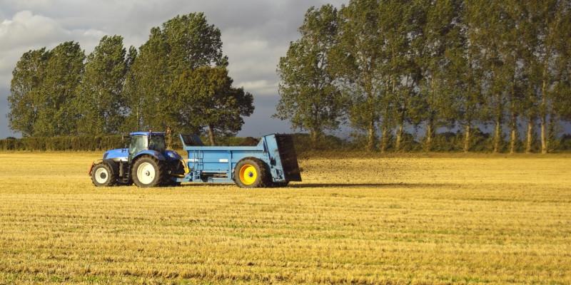A tractor spreading fertilizer on a field